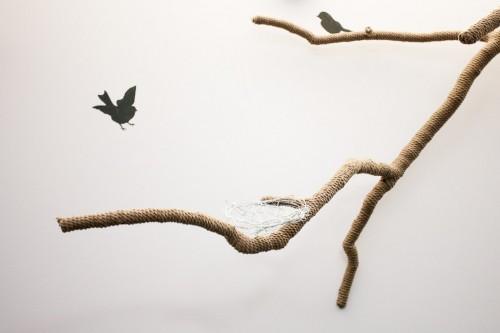 Pared decorada con ramas reales y pájaros pintados