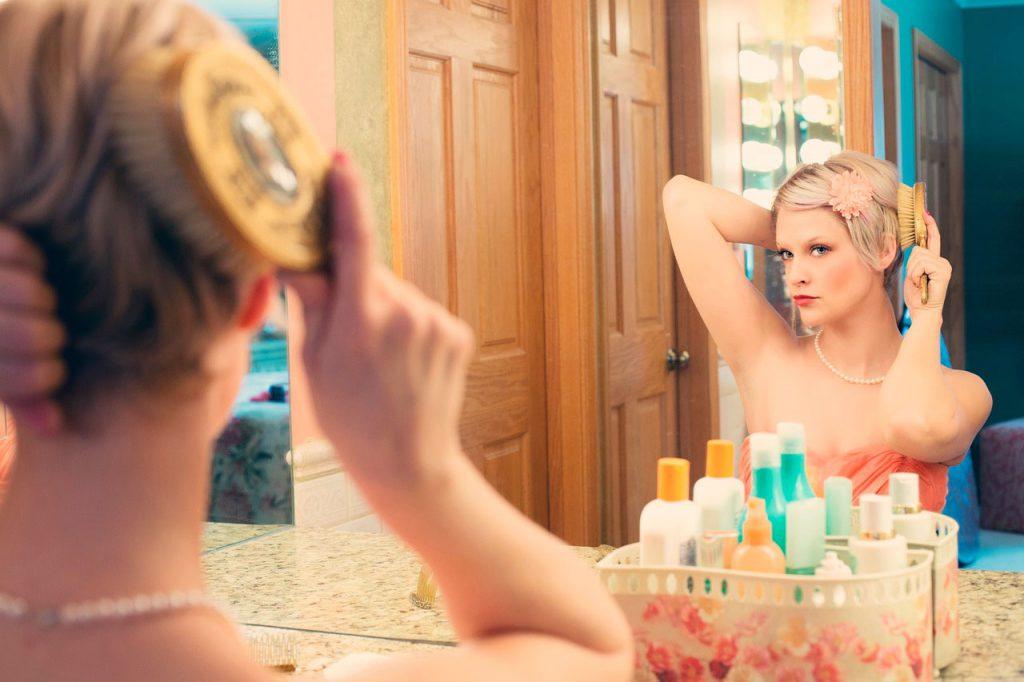 mujer practicando automaquillaje frente al espejo