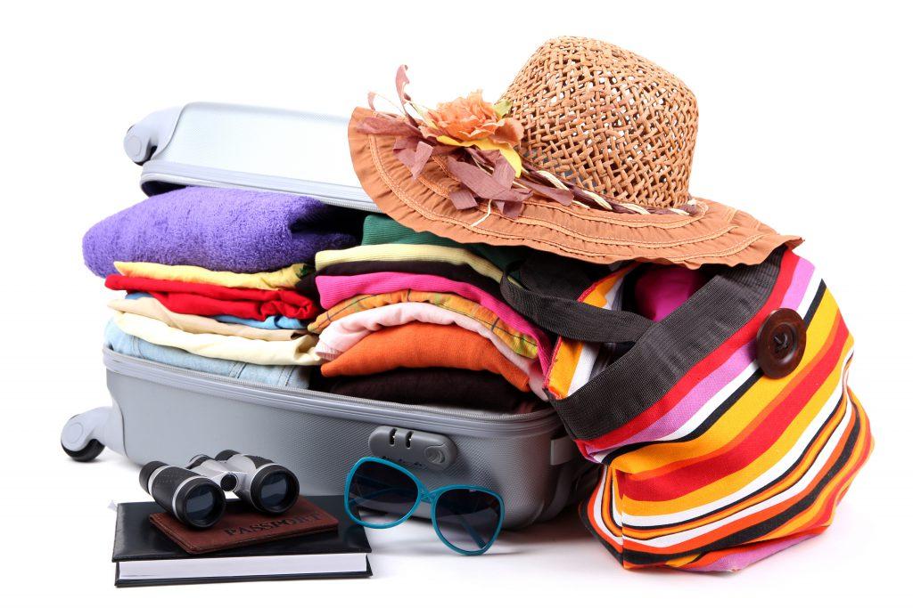 maleta de verano abierta repleta de ropa