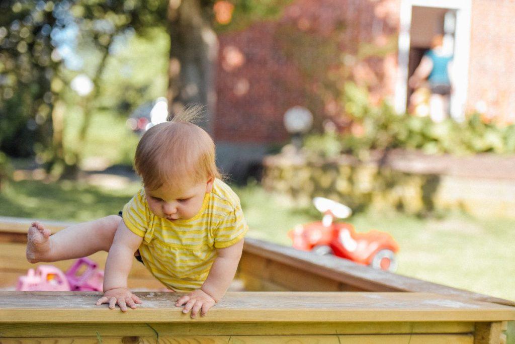 bebé jugando en el arenero de la escuela infantil